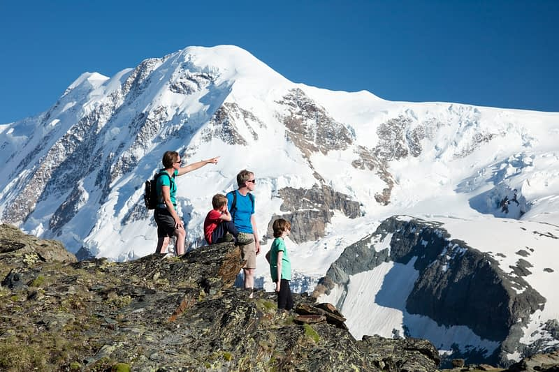Family hiking beneath Monte Rosa, Gornergrat, Zermatt, Switzerland.