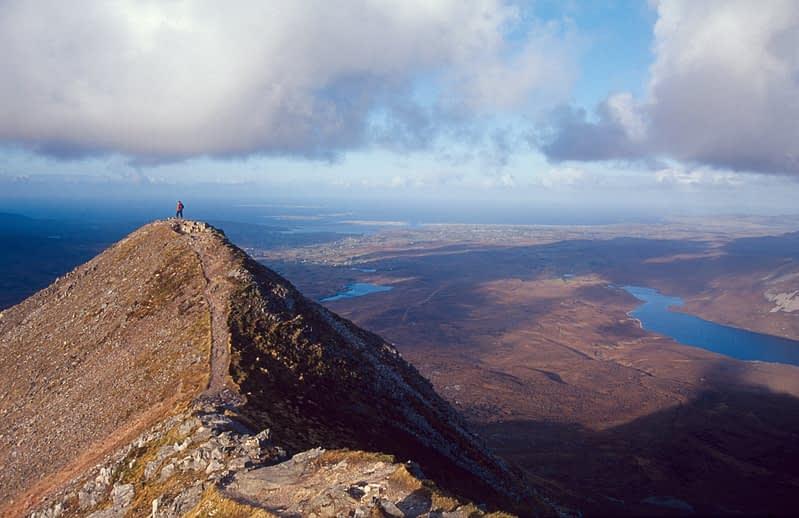 Walker at the summit of Errigal Mountain, Co Donegal, Ireland.