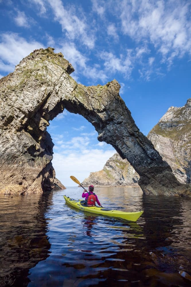 Sea kayaking beneath a natural arch near Sturrall, Glencolmcille, County Donegal, Ireland.