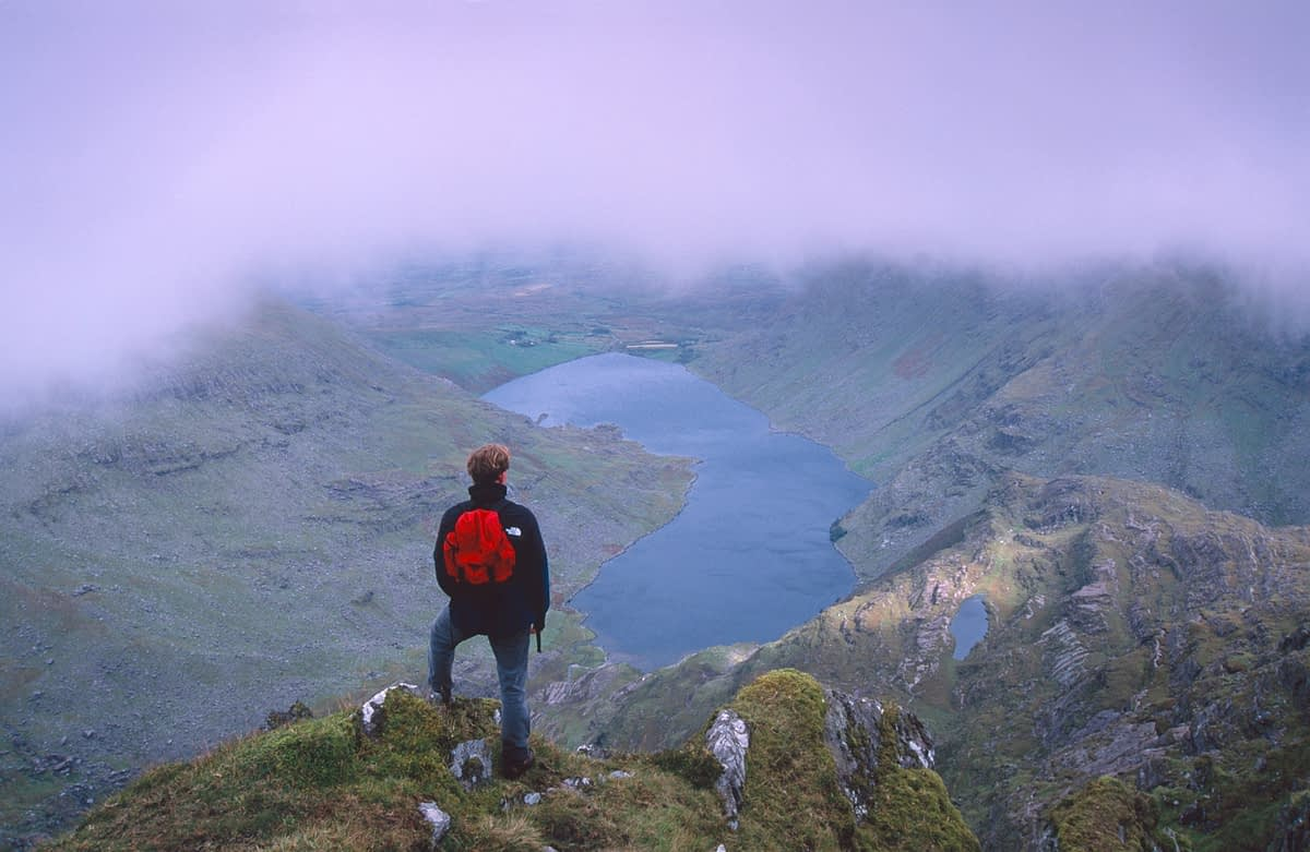 Walker looking over cloud-topped Coomasaharn, Co Kerry, Ireland.