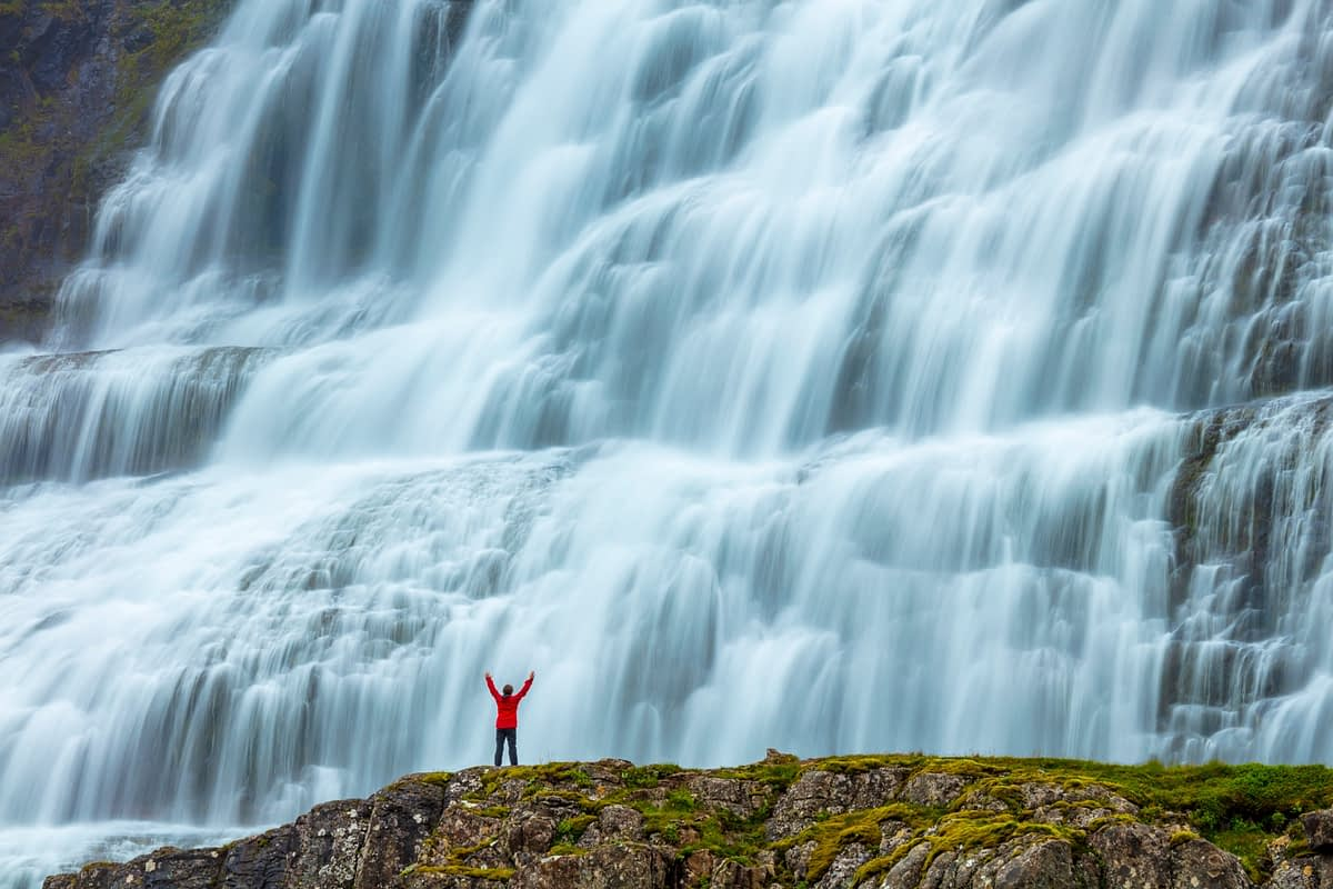 Person dwarfed by Dynjandi waterfall, or Fjallfoss, Westfjords, Iceland.