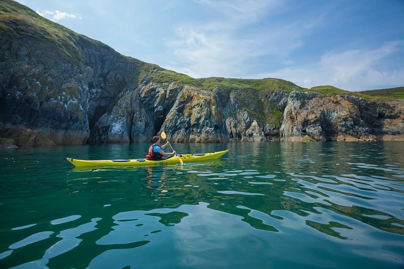 Sea kayaker beneath the cliffs of Howth Head, County Dublin, Ireland.