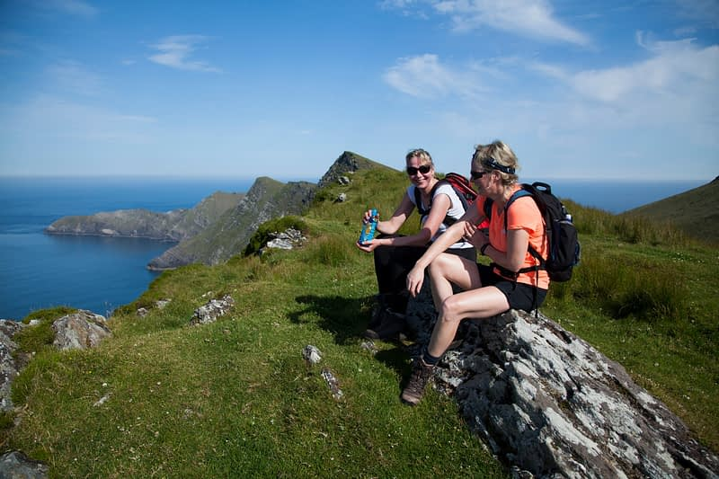 Hikers resting above Achill Head, Achill Island, County Mayo, Ireland.