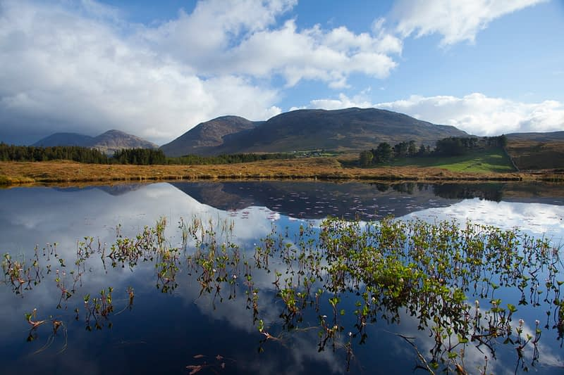 The Maumturk Mountains reflected in a lough. Connemara, County Galway, Ireland.
