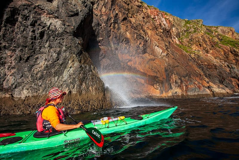 Sea kayaker beside a blow-hole rainbow, Arranmore Island, County Donegal, Ireland.