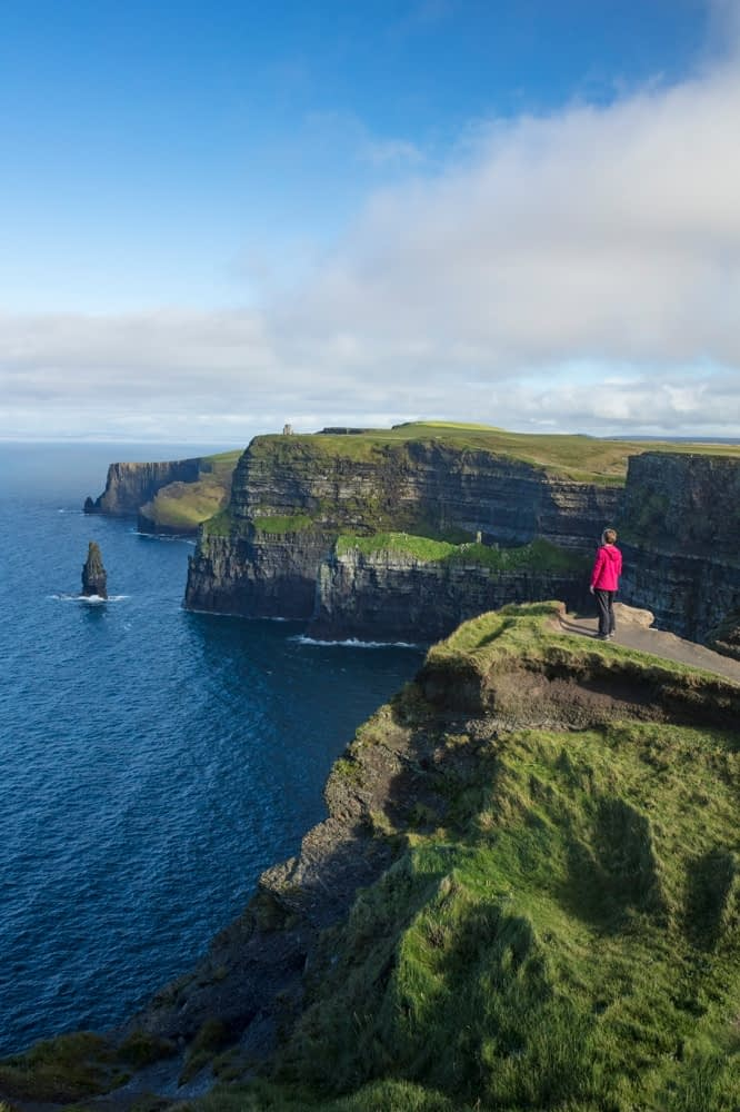 Hiker looking over the Cliffs of Moher from the south, County Clare, Ireland.