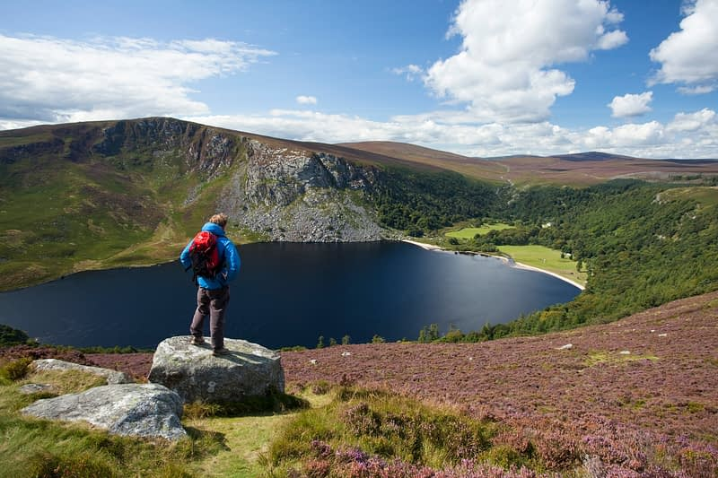 Walker admiring the view over Lough Tay, Wicklow Mountains, Co Wicklow, Ireland.