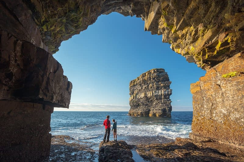 People viewing Dun Briste sea stack from a cave beneath Downpatrick Head. County Mayo, Ireland.