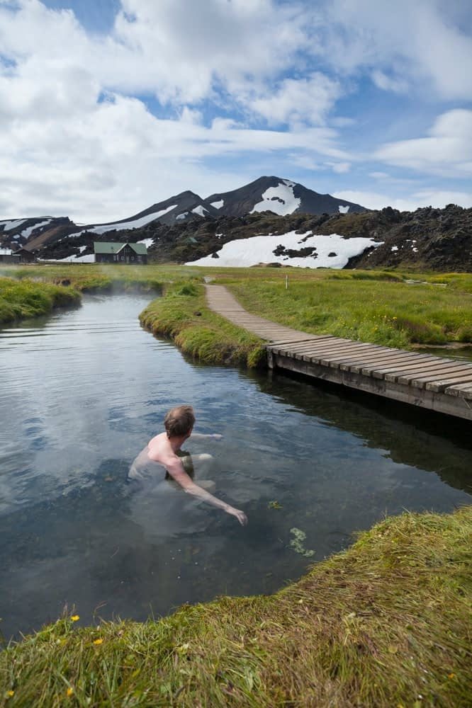 Swimmer enjoying the hot springs at Landmannalaugar, Sudhurland, Iceland.