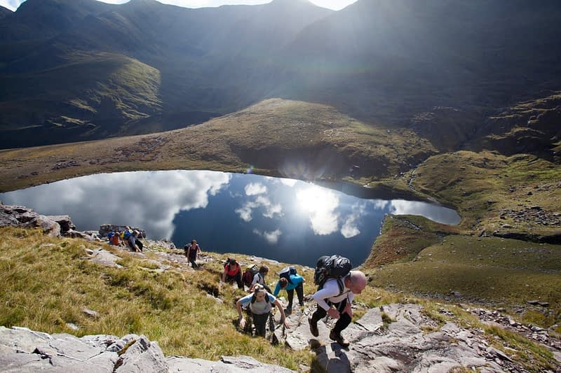 Walkers above Lough Gouragh on the ascent of Carrauntoohill, MacGillycuddy's Reeks, County Kerry, Ireland.