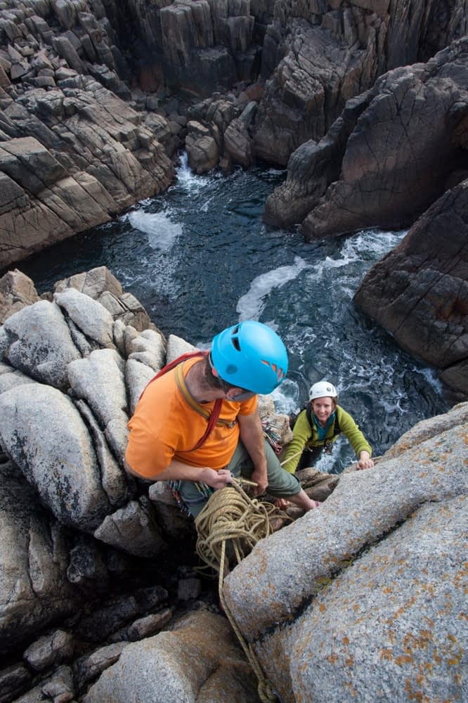 Rock climbers on a sea stack near Gwedore, County Donegal, Ireland.
