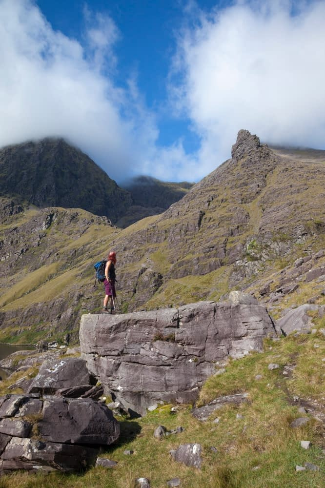 Hiker beneath Carrauntoohil from Lough Gouragh, MacGillycuddy's Reeks, County Kerry, Ireland.