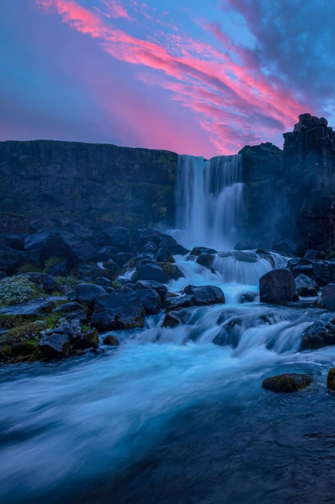 Sunset over Oxararfoss waterfall and the Almannagja cliffs, Pingvellir National Park, south Iceland.