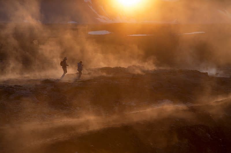 Sunset hikers amid the smouldering lava field at Leirhnjukur, Krafla volcano, Myvatn, Nordhurland Eystra, Iceland.