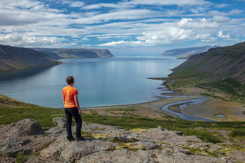 Person admiring the view over Arnarfjordur fjord from Nordfjall. Westfjords, Iceland.