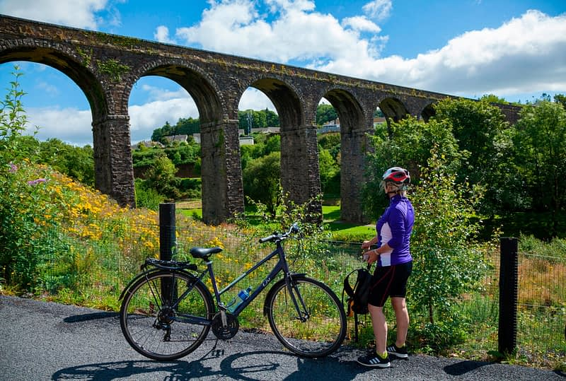 Cyclist beneath Kilmacthomas Viaduct, Waterford Greenway, County Waterford, Ireland.