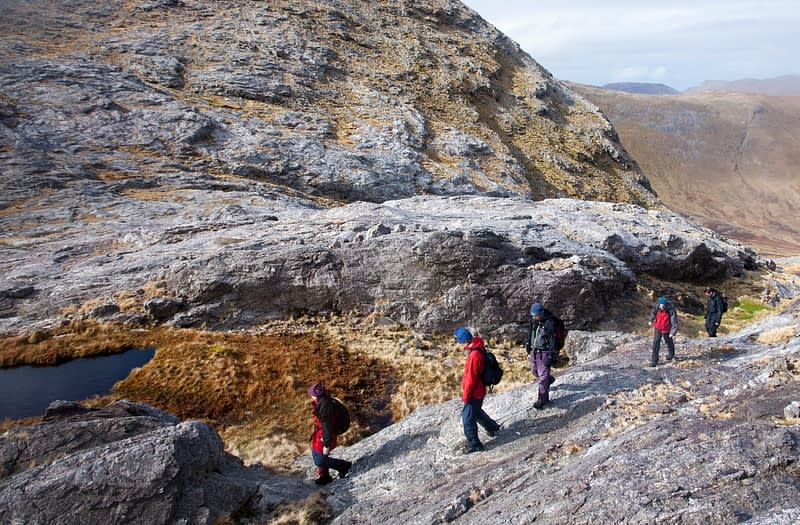 Walkers in Mám na bhFonsa, heading for Bencollaghduff, Twelve Bens, Connemara, Co Galway, Ireland.