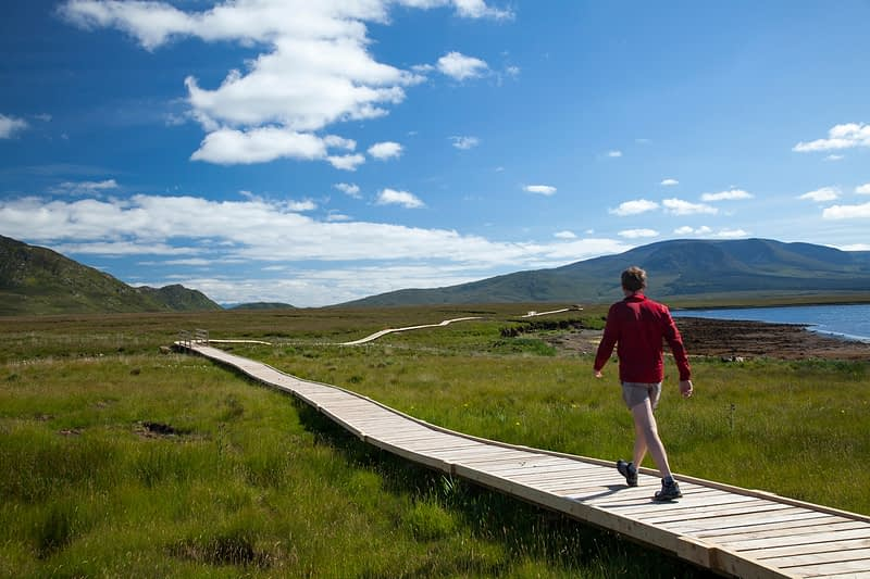 Hiker on a wooden walkway in Ballycroy National Park, County Mayo, Ireland.