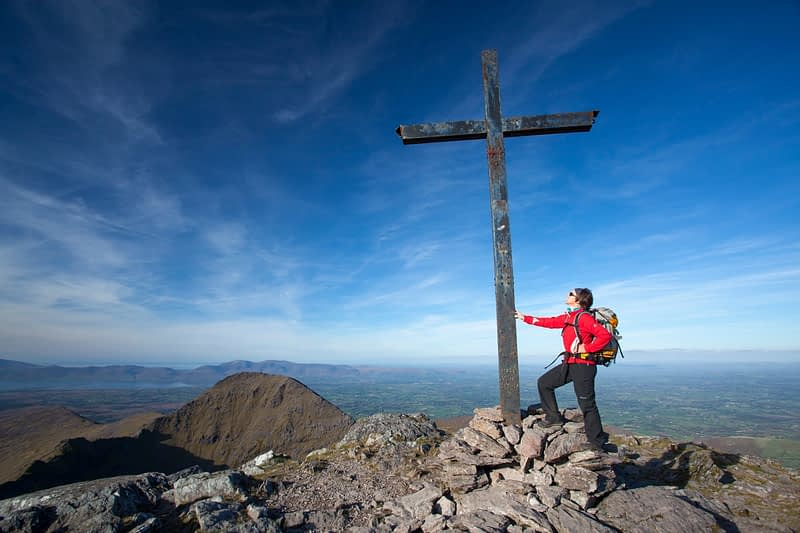 Walker at the summit of Carrauntoohil, MacGillycuddy's Reeks, County Kerry, Ireland.