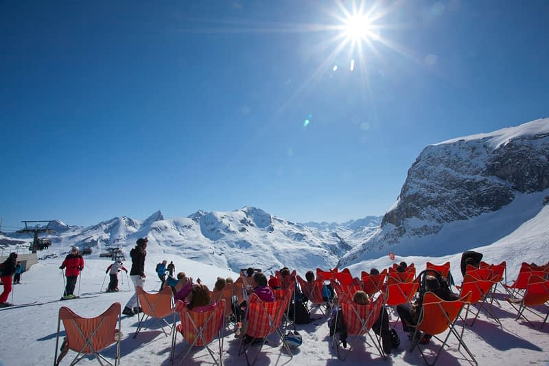 Skiers sun bathing high above Zurs, Arlberg, Austria.