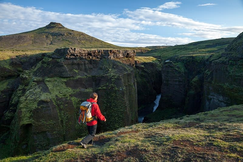 Hiker beside the upper Skoga river, Fimmvorduhals trail, Sudhurland, Iceland.