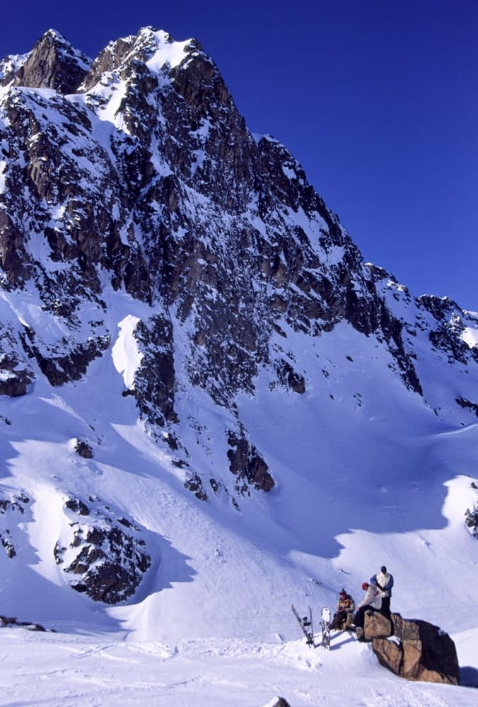 Off-piste snowboarders relaxing above the resort of La Mongie, French Pyrenees, France.