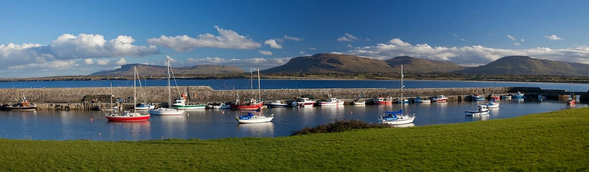 Sailing boats in Mullaghmore harbour beneath the Sligo Hills, Co Sligo, Ireland.