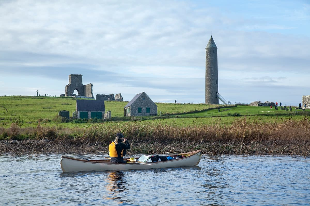 Canoeist beside Devenish Island, Lower Lough Erne, County Fermanagh, Northern Ireland.