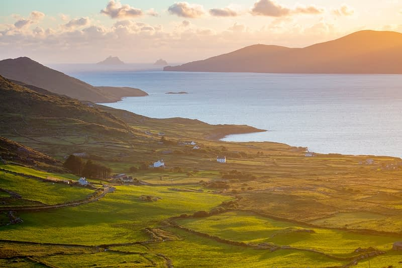 Evening light over fields and Skellig Islands from Ballinskelligs Bay, County Kerry, Ireland.