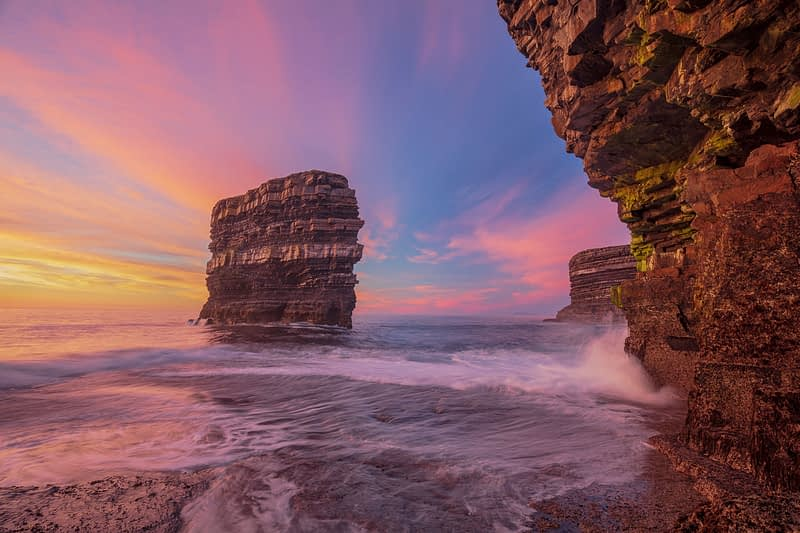 Sunset at Dun Briste sea stack from a cave beneath Downpatrick Head. County Mayo, Ireland.