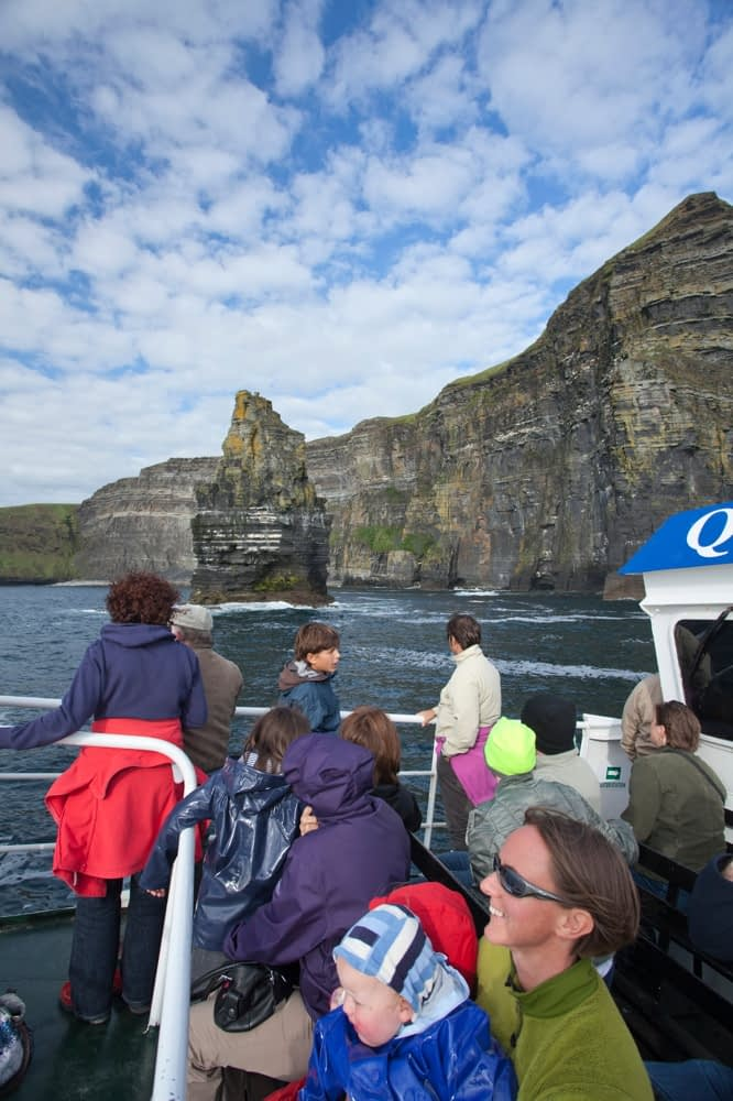 Tourists admiring the Cliffs of Moher from a scenic boat tour, Co Clare, Ireland.