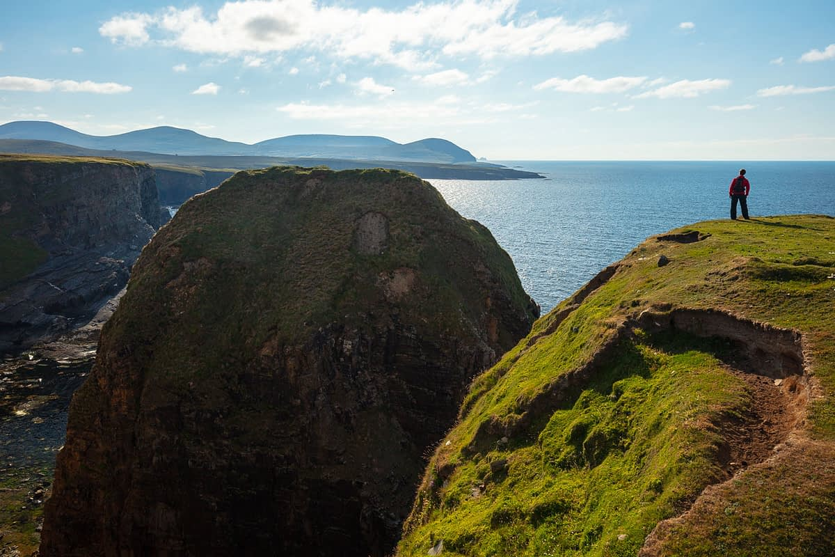 Person on top of sea cliffs near the Ceide Fields, North County Mayo, Ireland.