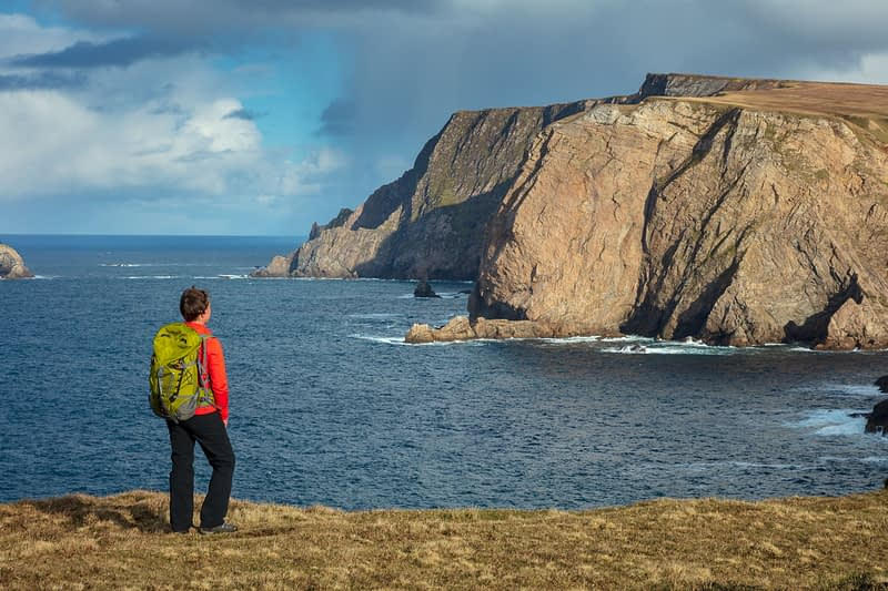 Coastal walker admiring the 260m sea cliffs of Benwee Head. Carrowteige, County Mayo, Ireland.