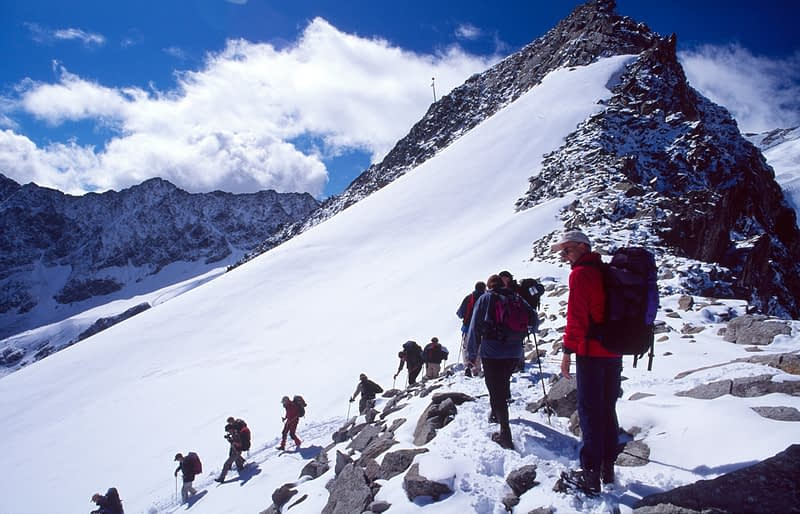 Walkers descending from Pitzaler Joch after a summer snow storm, Otztal Alps, Tirol, Austria.