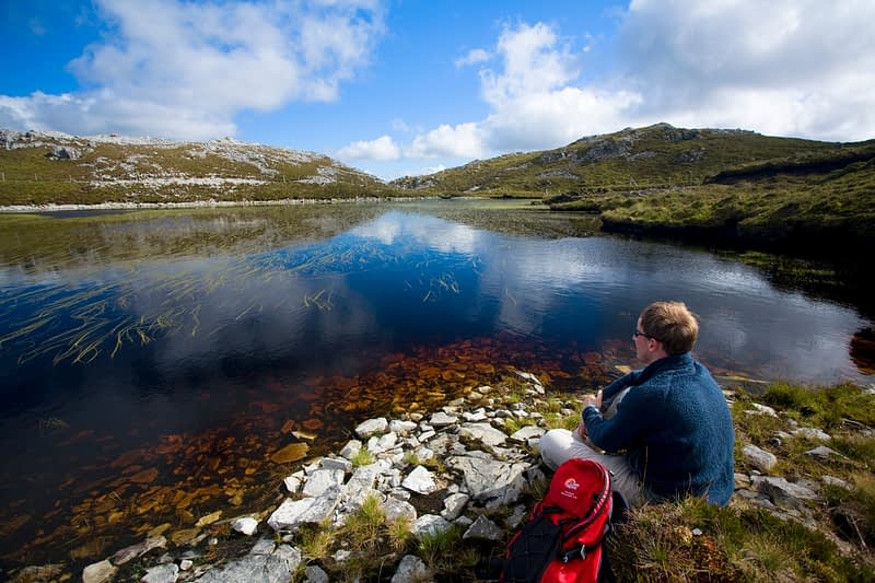 Walker resting beside a mountain pool, Aghla Mountain, Co Donegal, Ireland.
