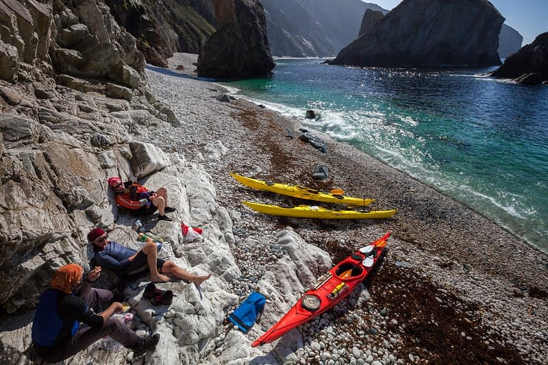 Sea kayakers relaxing on a storm beach beneath Slieve Tooey, County Donegal, Ireland.
