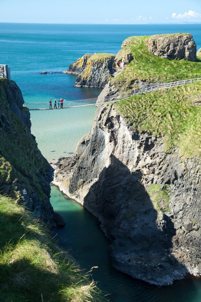 People crossing Carrick-a-rede Rope Bridge, Causeway Coast, County Antrim, Northern Ireland.