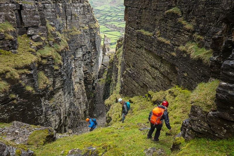 Hikers nearing the bottom of Annach Re Mhor chasm, Kings Mountain, County Sligo, Ireland.
