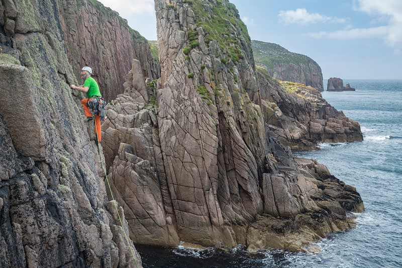 Rock climber on the eastern shore of Owey Island, County Donegal, Ireland.