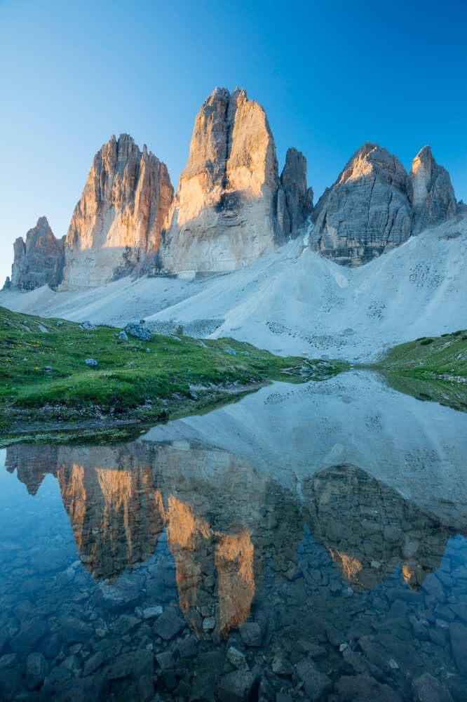 Dawn reflection of Tre Cime di Lavaredo, Sexten Dolomites, South Tyrol, Italy.