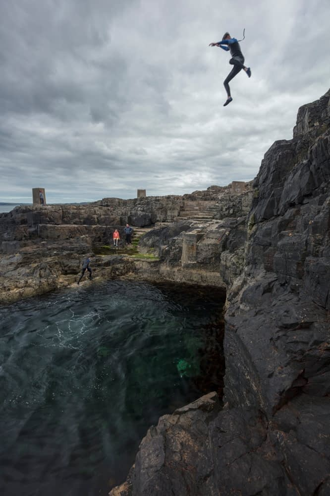 Cliff jumping at the Blue Pool, Portrush, County Antrim, Northern Ireland.
