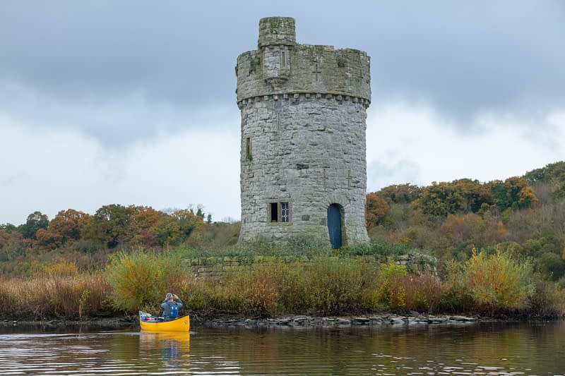 Canoeist beneath Crichton Tower, Crom Estate, Upper Lough Erne, County Fermanagh, Northern Ireland.