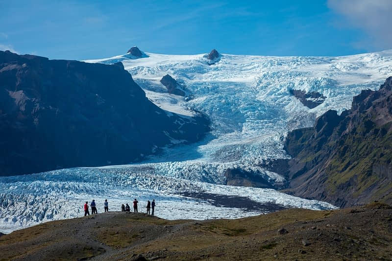 People dwarfed beneath the ice fall of Kviarjokulll glacier. Vatnajokull ice cap, Sudhurland, south east Iceland.