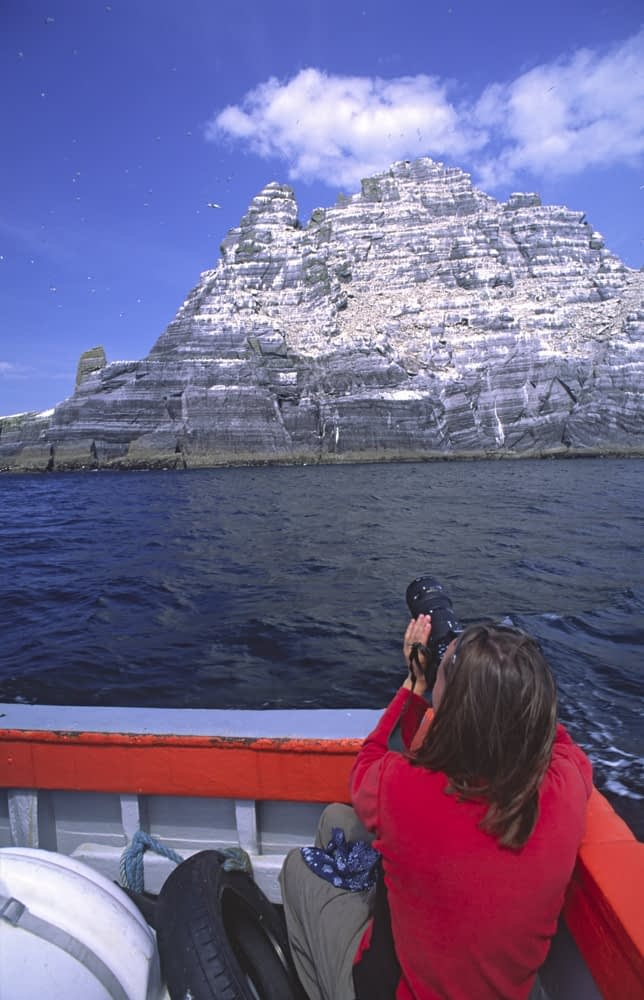 Tourist on a boat in front of Little Skellig, Skellig Islands, Co Kerry, Ireland.