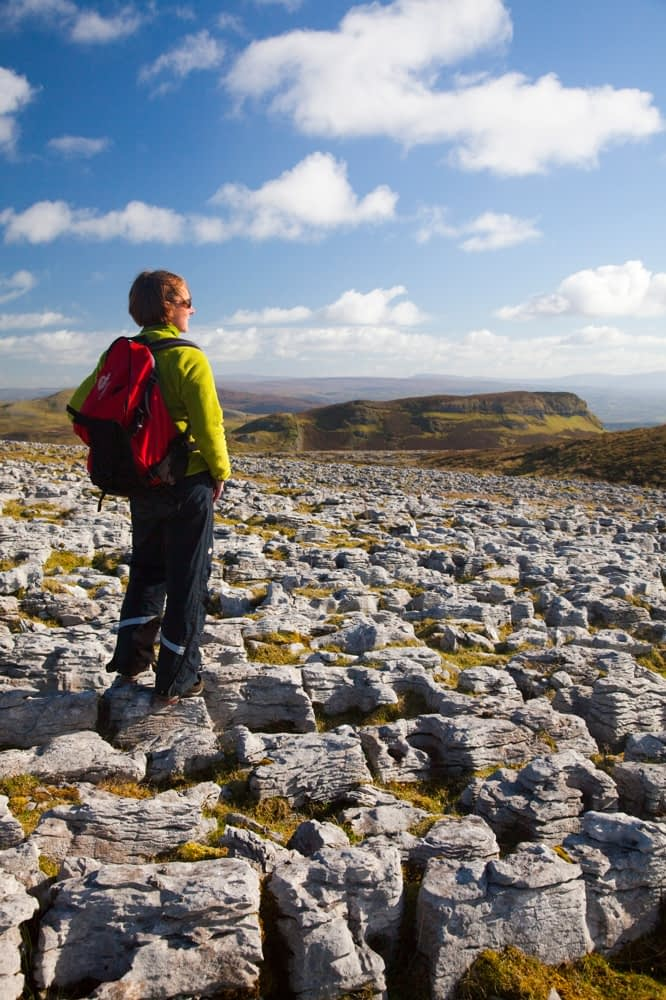 Walker on limestone pavement, Keelogyboy Mountain, Co Leitrim, Ireland.