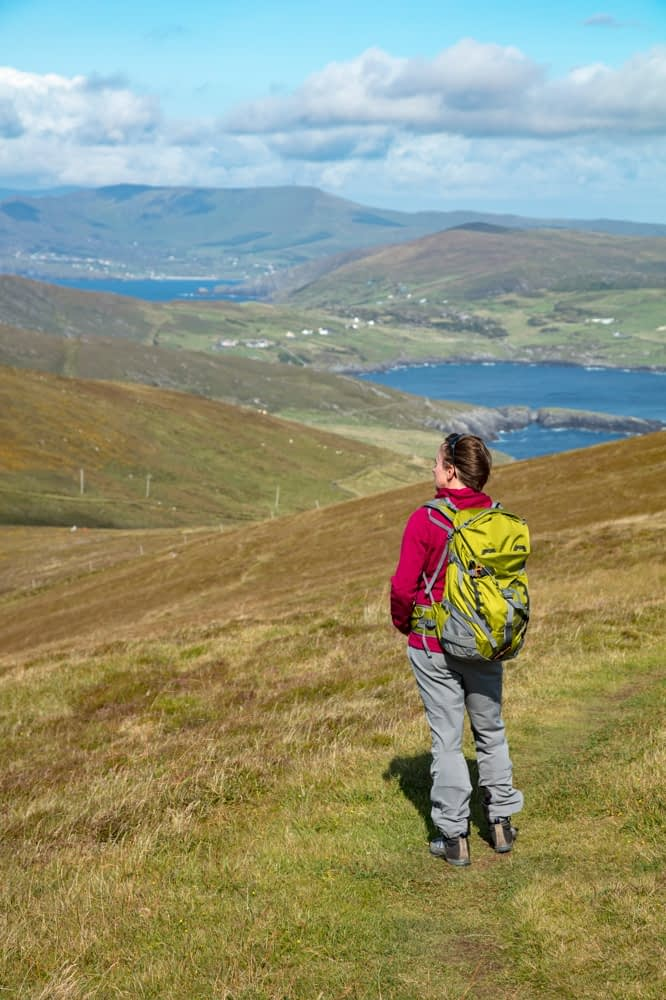 Hiker on the slopes of Cnoc Bolais, Dursey Island, Beara Peninsula, County Cork, Ireland.