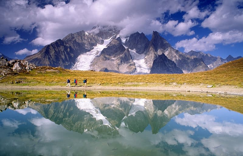 Walkers reflected beneath Mt Blanc, Tour of Mont Blanc, Italian Alps, Italy.