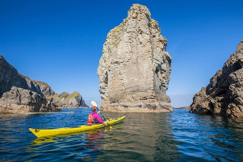 Sea kayaking past a massive stack near Port, Glencolmcille, County Donegal, Ireland.