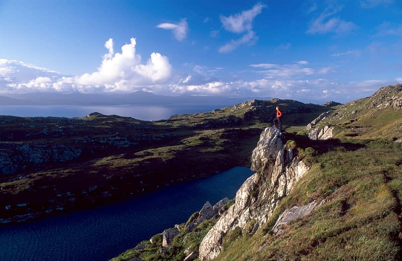 Walker looking over Lough Akeen, Sheep's Head Way, Co Cork, Ireland.