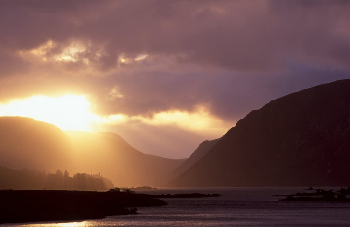 Sun breaking through storm clouds over Lough Veagh, Glenveagh National Park, Co Donegal, Ireland.